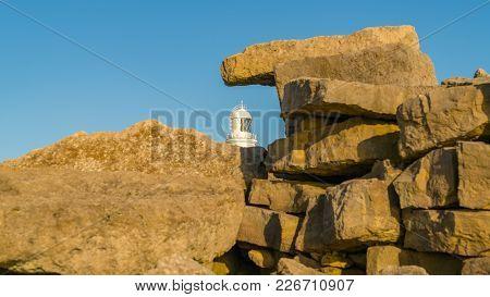 Portland Bill Lighthouse Seen Through The Rocks Near Pulpit Rock, Jurassic Coast, Dorset, Uk