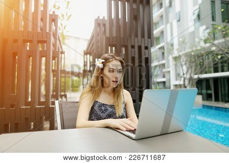 Beautiful Summer Portrait Of Girl, Who Are Clapping Laptop Near Pool. Young Woman Is Working As Tran