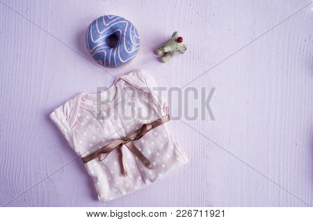 Female Clothes And Accessories For The Newborn, Flat Lay On Pink Wooden Background.