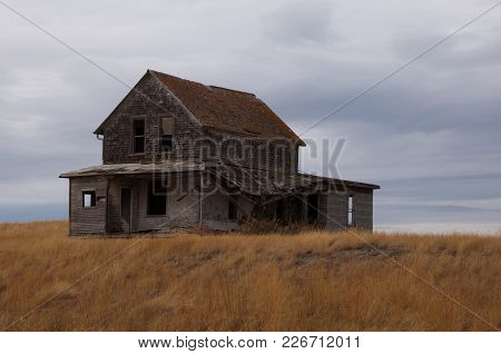 Abandoned Homestead On A Golden Field With Grey Skies
