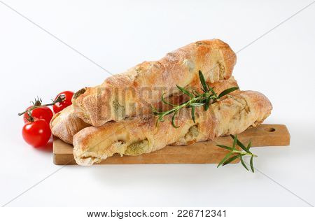 loaves of olive ciabatta bread, rosemary and cherry tomatoes on wooden cutting board