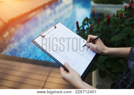 Close-up Of Woman's Hand Fills Out Visa Application Form To France On Background Of New Pool With Su