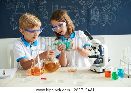 Girl Pouring Reagent Into Flask With Yellow Reagent Her Classmate Holding