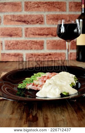 Green Asparagus Wrapped Into Smoked Bacon Covered With White Sauce On A Black Plate