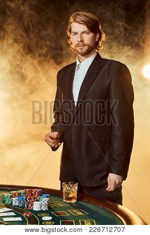 A Man In A Business Suit Standing Near The Game Table. Male Player. Passion, Cards, Chips, Alcohol,