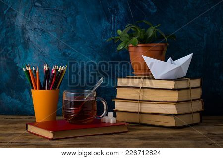 A Pile Of Books, A Cup Of Hot Tea, A Paper Boat, Colored Pencils On A Darkly Blue Background