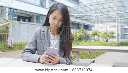 Businesswoman using mobile phone over green background