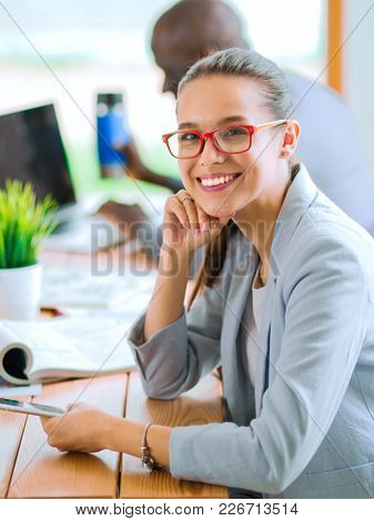 Business woman sitting in her office using a tablet computer. Business woman. Meeting