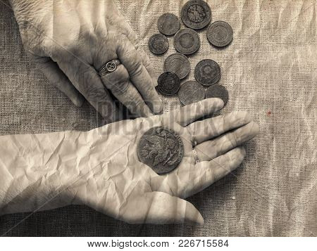 Hands Of Old Woman, Magnifying Glass  And Money.selective Soft Focus.the Concept Of Poverty In Retir