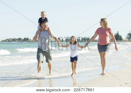 Young Happy And Beautiful Family Mother Father Holding Hand Of Son And Daughter Walking Joyful On Th