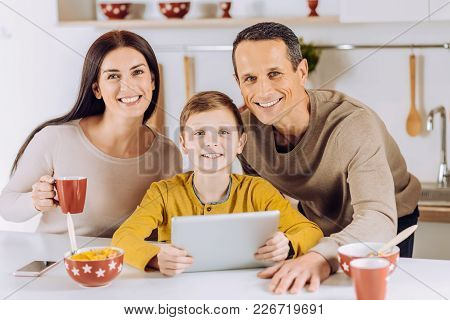 Happy Family. Pleasant Upbeat Young Family Posing For The Camera While Watching A Video On Tablet To