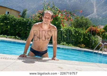 Young Man Swimming And Relaxing In Pool On Summer Vacation