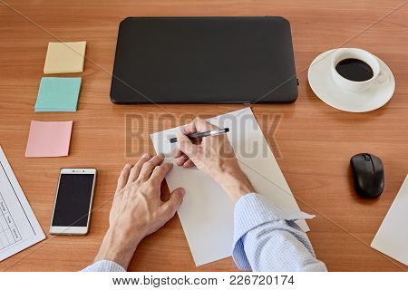 Top View Of Laptop, Smartphone, Cup Of Coffee And Male Hand Writing On Sheet Of Paper