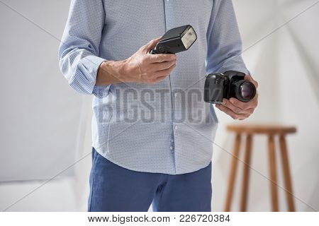 Closeup Of Young Man Holding Digital Camera With Synchronizer And Flash In Studio, Focus Is On Hand