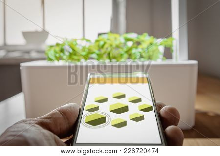 Closeup Of Male Hand Holding Remote To Control Plant Growth, Focus Is On Smart Remote