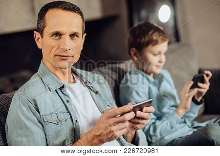 Avid Gamer. Handsome Pleasant Man Sitting On The Sofa Next To His Pre-teen Son And Posing For The Ca