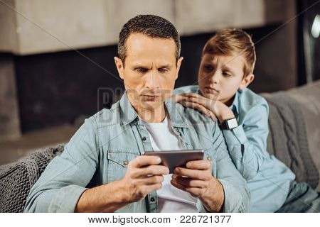 Pay Attention. Upset Pre-teen Boy Cuddling To His Father On The Sofa, Watching Him Play On The Phone