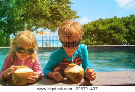 Little Boy And Girl Drinking Coconut Cocktail On Tropical Beach Resort