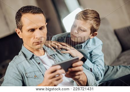 Notice Me. Sad Pre-teen Boy Searching Attention From His Father And Cuddling To Him While The Man Pl