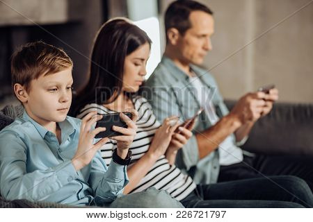 Addicted Users. Pleasant Little Boy Sitting On The Sofa Next To His Parents And Playing On His Phone