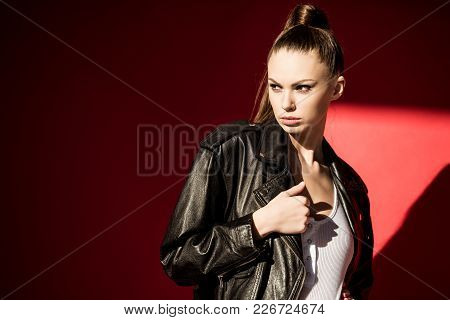 Beautiful Girl Posing In Black Leather Jacket For Fashion Shoot On Red