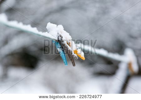 Colorful Clips For Washing Laundry Covered With Snow On Strip Rope Outdoor. Winter Housework Concept