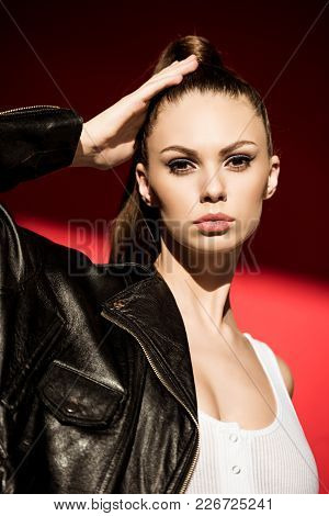 Portrait Of Stylish Girl With Ponytail Hairstyle Posing For Fashion Shoot On Red