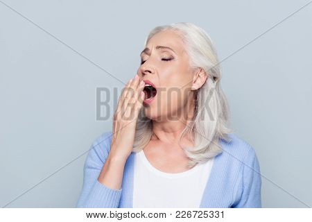 Portrait Of Tired, Bored, Attractive, Aged, Lazy Woman In  Closing Her Open Mouth With Palm, She Wan