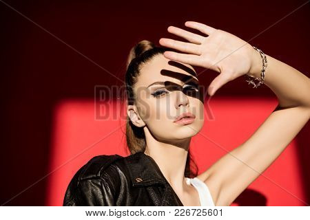 Attractive Fashionable Girl Gesturing And Posing For Fashion Shoot On Red