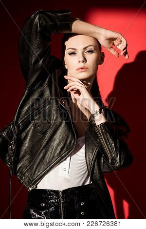 Stylish Young Woman Posing In Black Leather Jacket For Fashion Shoot On Red