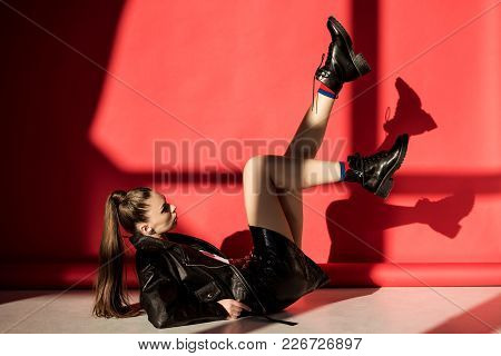 Stylish Woman Posing In Black Leather Jacket For Fashion Shoot On Red