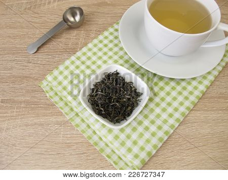 Cup Of Chinese Tea White Monkey And Loose Tea Leaves