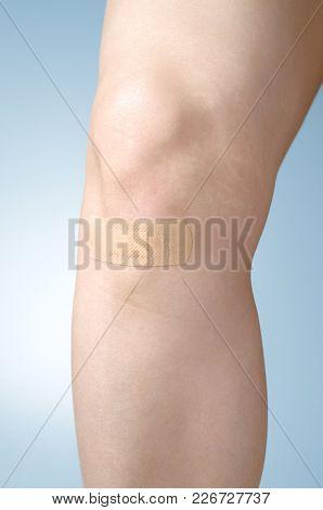 Female Leg With Adhesive Bandage On Blue Background
