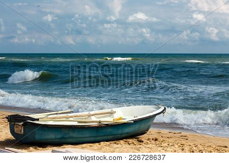 Old Row Boat On The Sandy Beach At Sunny Day. Windy Weather, Waves In The Sea Bay