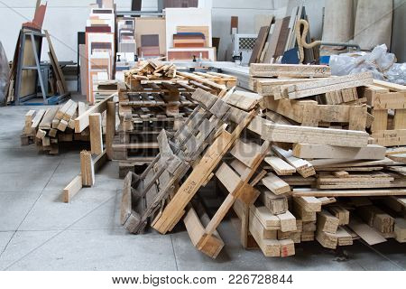 A Pack Of Parts Of A Particleboard In The Furniture Manufacturing. Warehouse With Wooden Pallets.