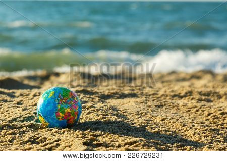 Globe Of The Planet  Earth On A Sandy Beach On A Ocean Background. Travel Around The World Concept.