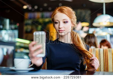 Young Woman Making Self Portrait Using Smartphone. Girl Making Selfie. Woman In Cafe. Woman Alone. S
