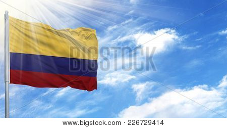 Flag Of Colombia On Flagpole Against The Blue Sky.