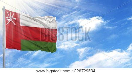 Flag Of Oman On Flagpole Against The Blue Sky.