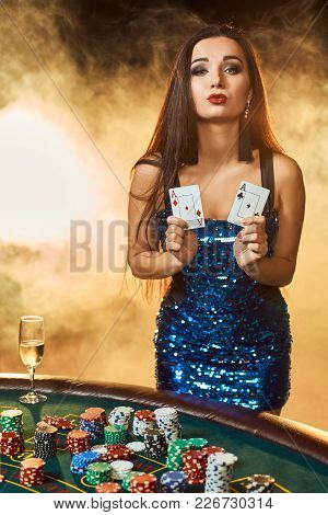 Young Beautiful Woman In A Blue Shiny Dress Poses Near Poker Table In Luxury Casino. Woman Player. P