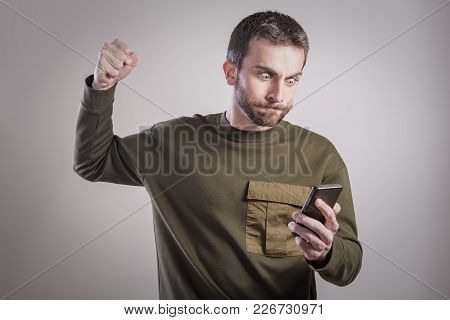 Young Man Angry And Furious With His Cell Phone, Shouting And Yelling In Shock