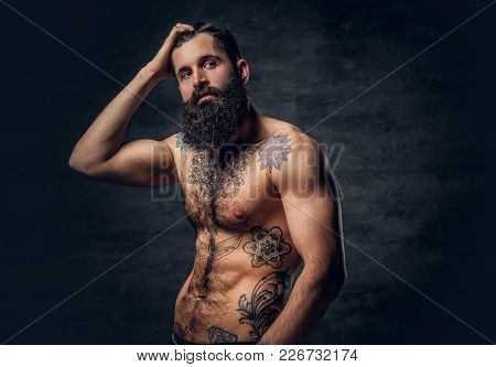 Shirtless Bearded Male With Tattooed Torso Posing Over Dark Grey Background.