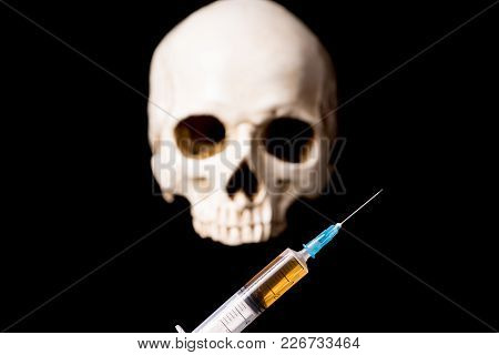 Syringe With Brown Liquid And Blurry Skull Isolated On Black Background