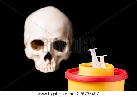 Medical Waste Container With Syring And Skull Isolated On Black Background