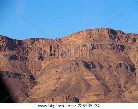 Rocky Atlas Mountains Range Landscape In Southeastern Morocco Near Old Village Of Oulad And Clear Bl