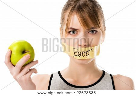 Young Woman With Stick Tape With Striked Through Word Food Covering Mouth Holding Apple Isolated On