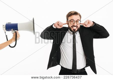 Image of confused businessman standing isolated over white background covering ears because of loudspeaker.