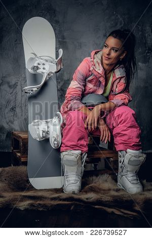 Positive Suntanned Sporty Female Posing With Snowboard In A Studio.