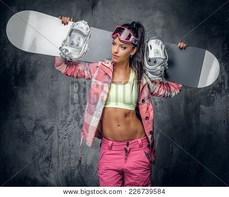 Attractive Sexual Female In Ski Costume Holding Snowboard On A Shoulder.