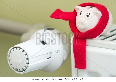 Save Money Heating Concept With Thermostat And Piggy Bank On Green Background
